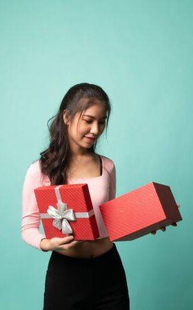 142674570-young-asian-woman-open-a-gift-box-on-cyan-background